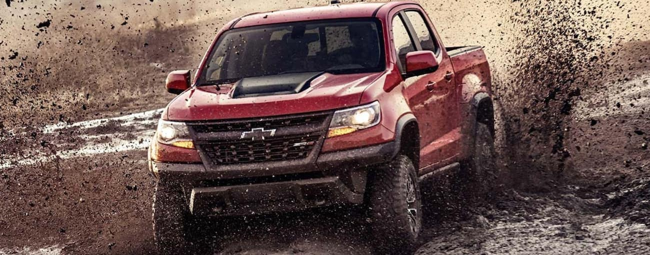 A red 2019 Chevy Colorado ZR2 is off-roading in the mud after winning the 2019 Chevy Colorado vs 2019 Ford Ranger comparison.