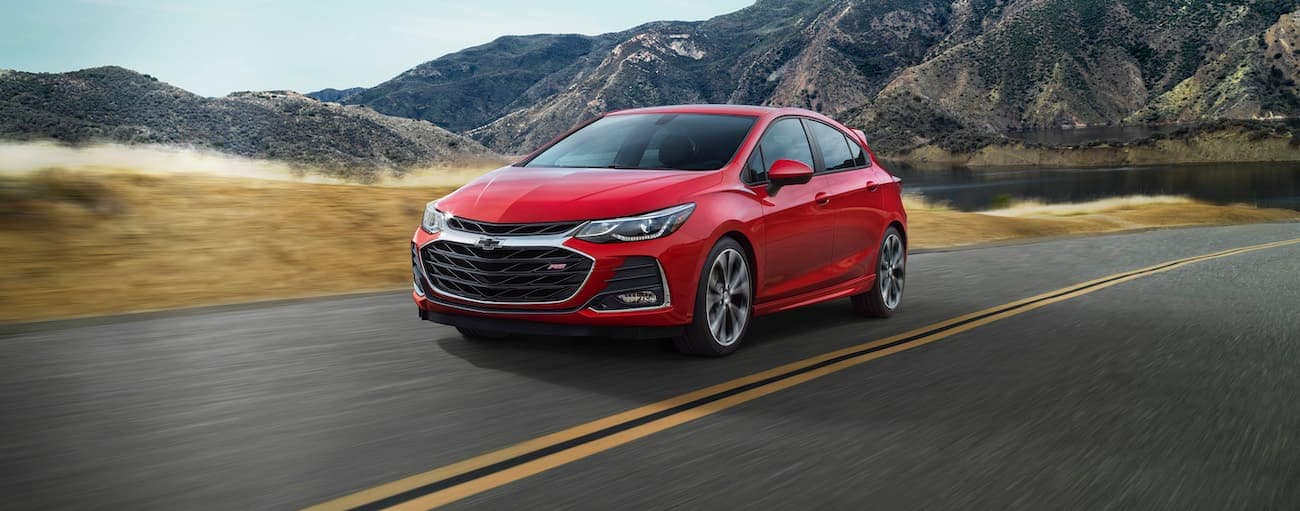 A red 2019 Chevy Cruze Hatchback is driving away from mountains after winning the 2019 Chevy Cruze vs 2019 Kia Forte comparison.