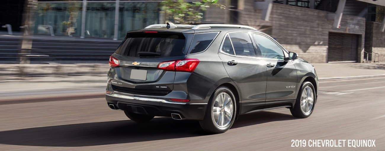 A grey 2019 Chevy Equinox is driving on a city street in Indianapolis, IN.