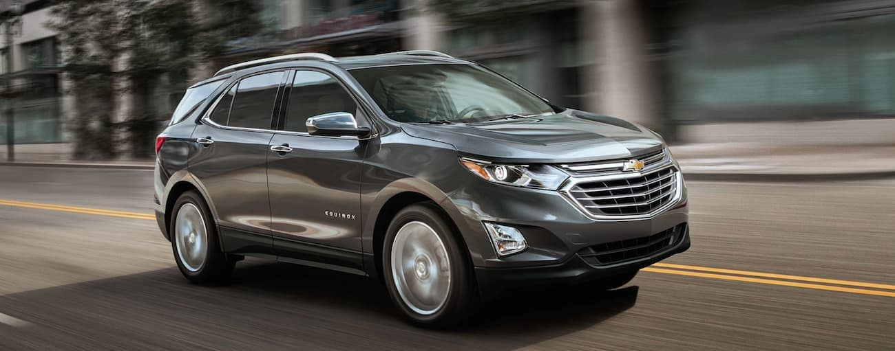 A grey 2019 Chevy Equinox is driving on a city street in Indianapolis, IN, after winning the 2019 Chevy Equinox vs 2019 Toyota RAV4 comparison.