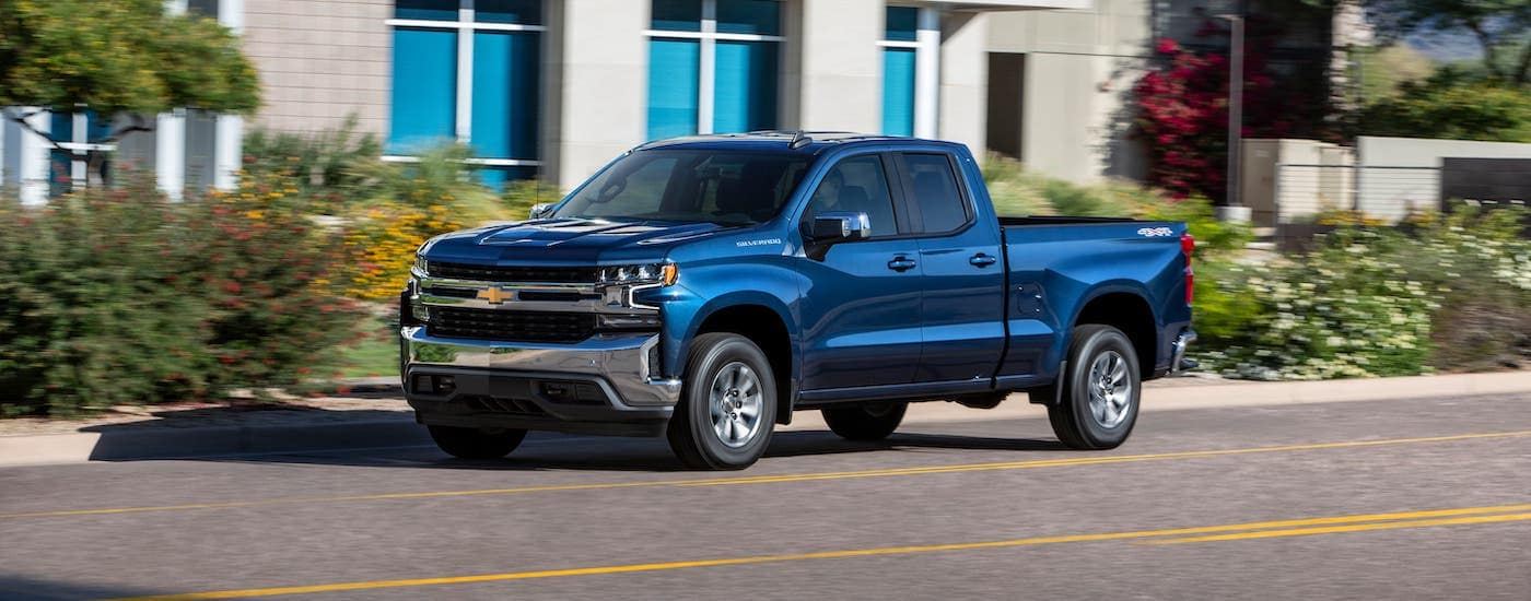 A blue 2019 Chevy Silverado is driving on a city street.