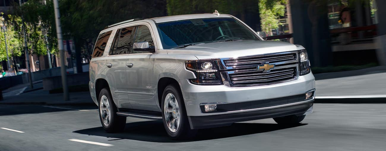 A silver 2019 Chevy Tahoe, which wins when comparing the 2019 Chevy Tahoe vs 2019 GMC Yukon, is driving on a city street in Indianapolis, IN.