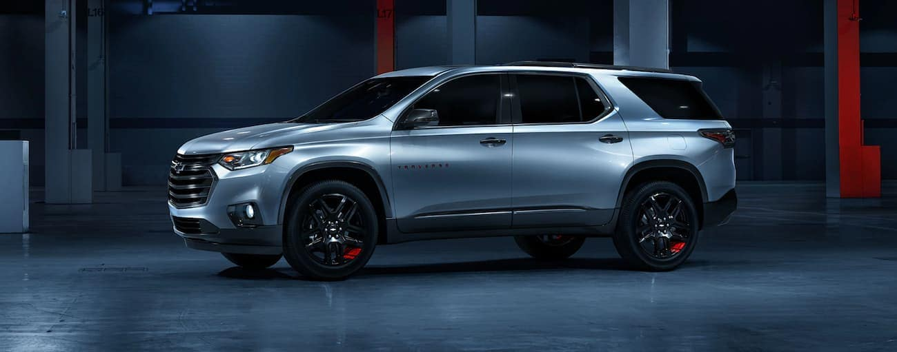 A silver special edition 2019 Chevy Traverse is in a dark showroom after winning the 2019 Chevy Traverse vs 2019 Ford Explorer comparison.