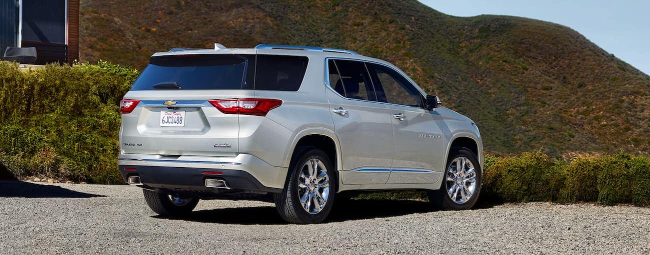A white 2019 Chevy Traverse is parked on gravel in front of a hill.