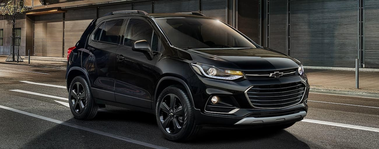 An all black 2019 Chevy Trax is parked on a city street at night after winning the 2019 Chevy Trax vs 2019 Hyundai Kona comparison.