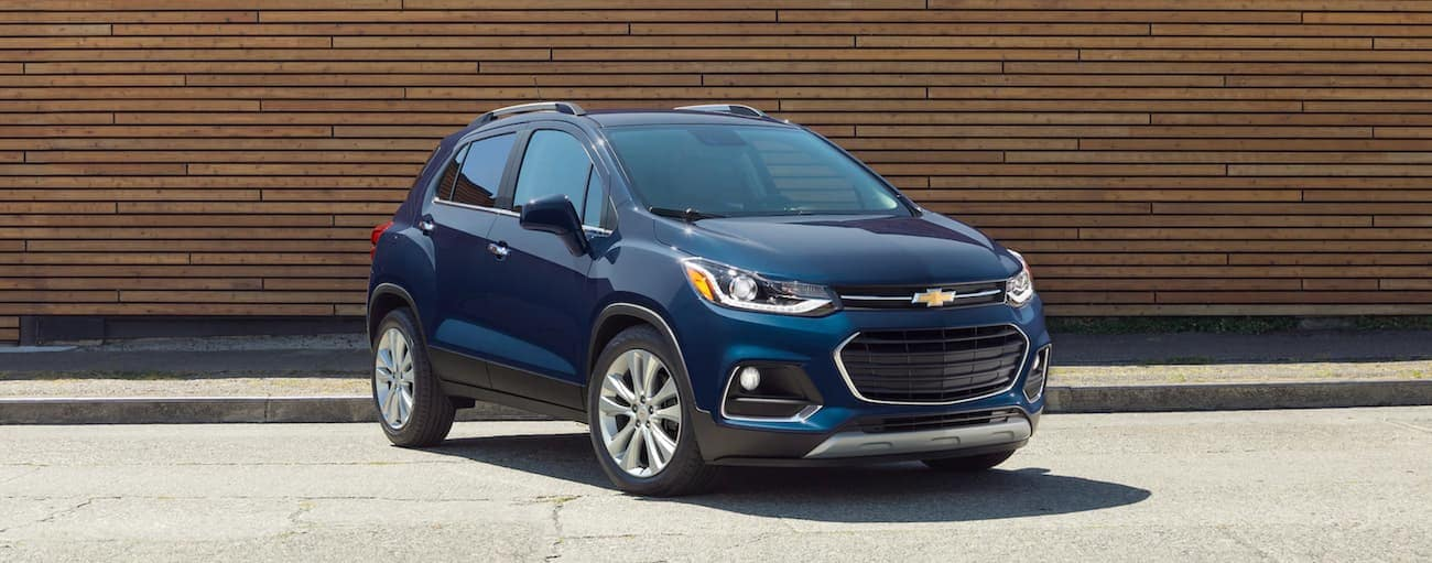 A blue 2019 Chevy Trax is parked in front of a wooden wall near Indianapolis, IN.