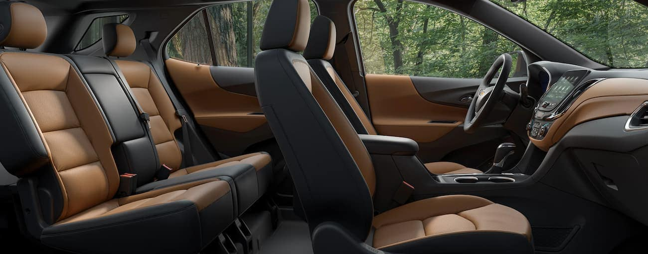 The black and tan interior of a 2020 Chevy Equinox is shown from the side.