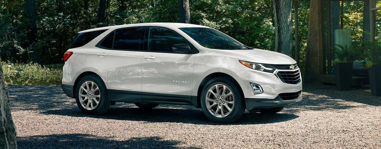 A white 2020 Chevy Equinox, which wins when comparing the 2020 Chevy Equinox vs 2020 Ford Escape, is parked on a gravel driveway near Indianapolis, IN.