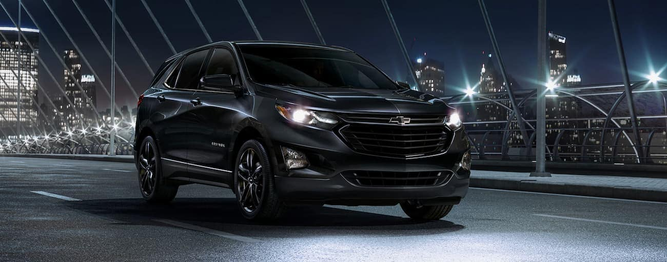 An all black 2020 Chevy Equinox is on a city bridge at night.