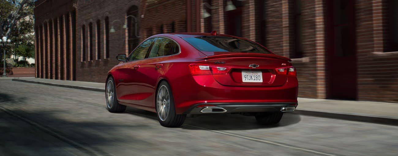 A red 2020 Chevy Malibu, which wins when comparing the 2020 Chevy Malibu vs 2020 Ford Fusion, is driving past a brick building in Indianapolis, IN.