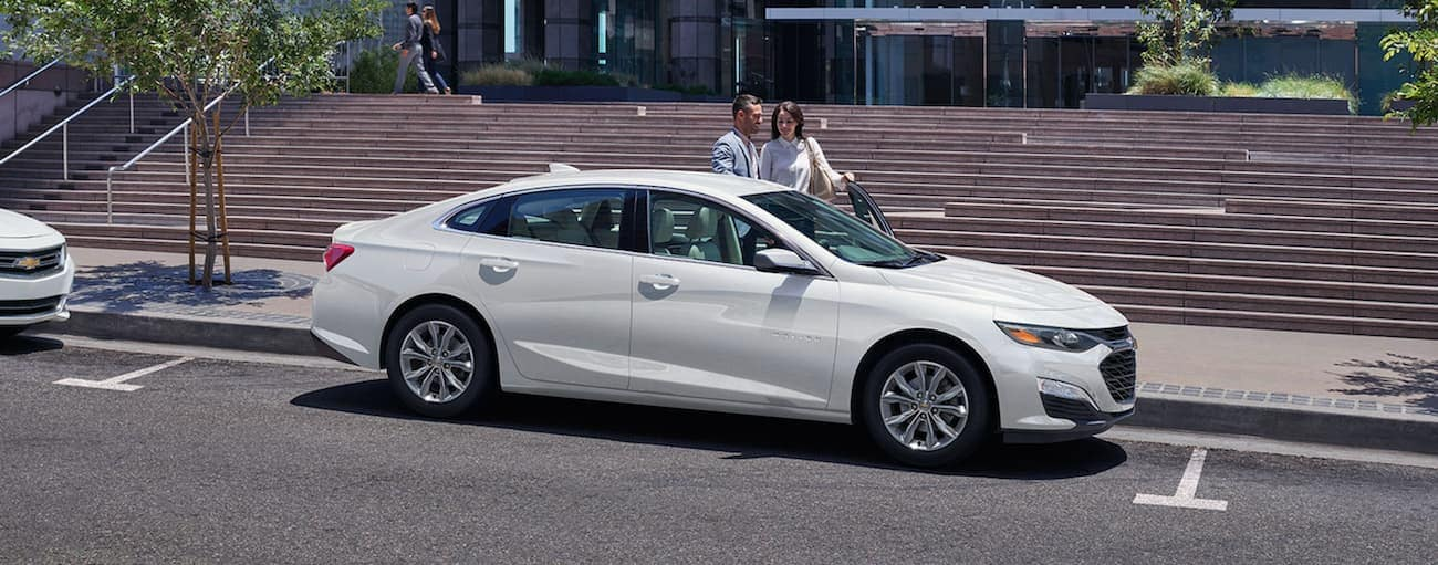 A couple is getting into a white 2020 Chevy Malibu parked on a city street in front of stairs.