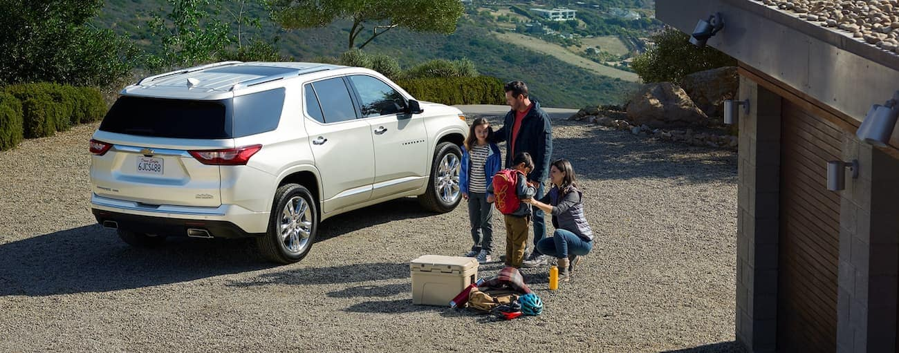 A family is next to a white 2020 Chevy Traverse outside a home with a view of hills.