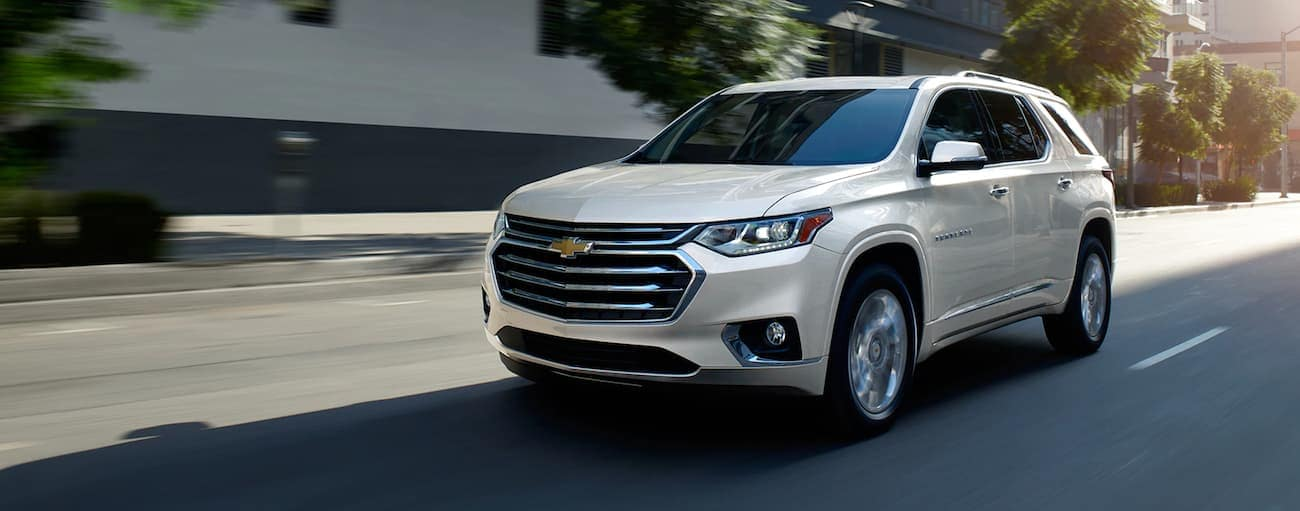 A white 2020 Chevy Traverse, which wins when comparing the 2020 Chevy Traverse vs 2020 GMC Acadia, is driving on a city street in Indianapolis, IN.