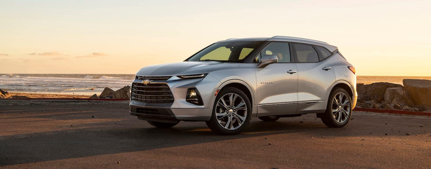 A silver 2019 Chevrolet Blazer Premier is parked at a beach at sunset.