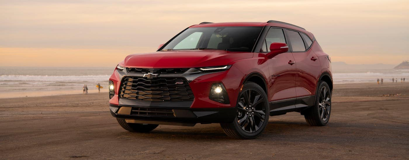 A red 2019 Chevrolet Blazer RS is parked on a beach at sunset.