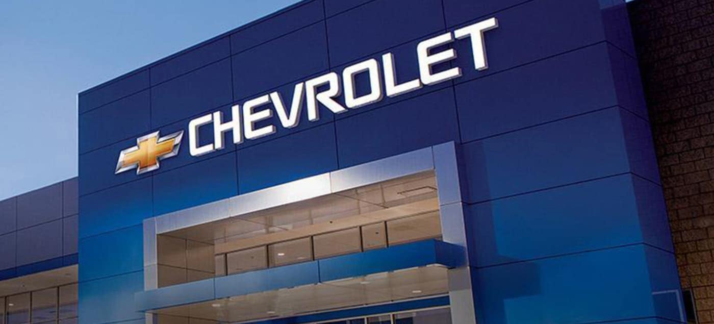 A Chevy Car dealership in Indianapolis, IN, is shown at dusk.