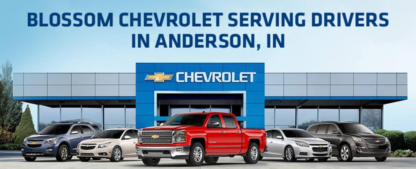 Five Chevy models are in front of a Chevrolet Dealership Near Anderson, IN, with 'Blossom Chevrolet Serving Drivers in Anderson, IN' written above.