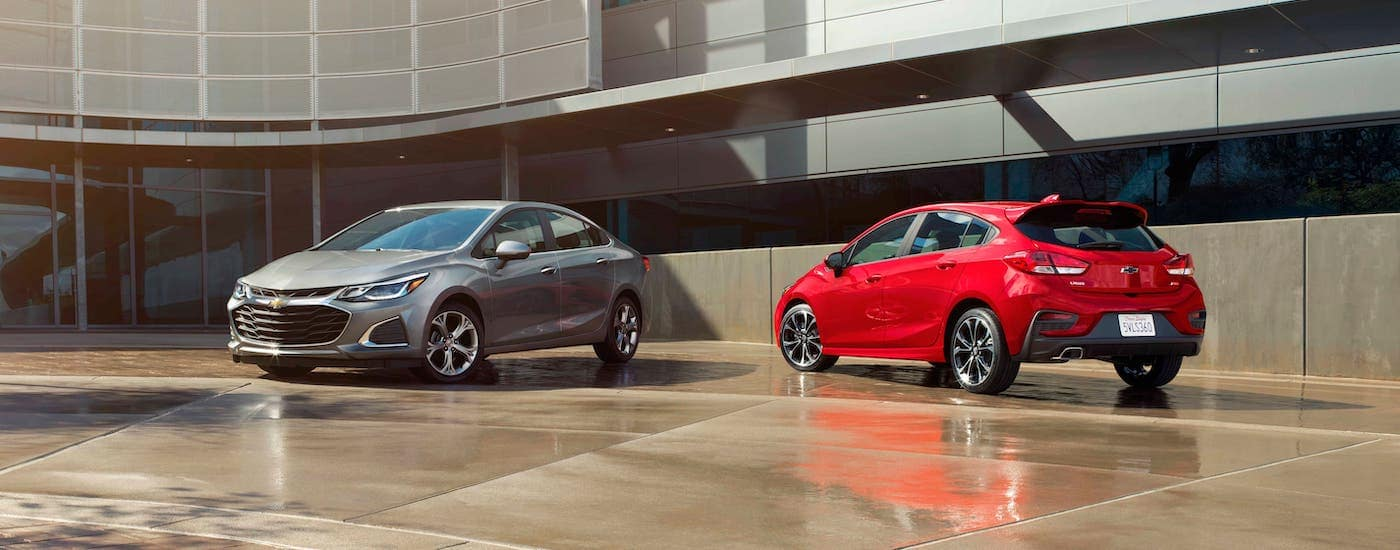A silver Chevy Cruze sedan and an red Chevy Cruze hatchback, both loaded with tech features, are parked in front of an office building in Indianapolis, IN.