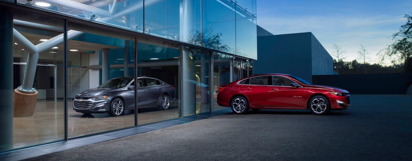 A silver 2020 Chevy Malibu is parked inside an Indianapolis, IN, showroom while a red Malibu is parked outside. Find both at a Chevy dealer near me.
