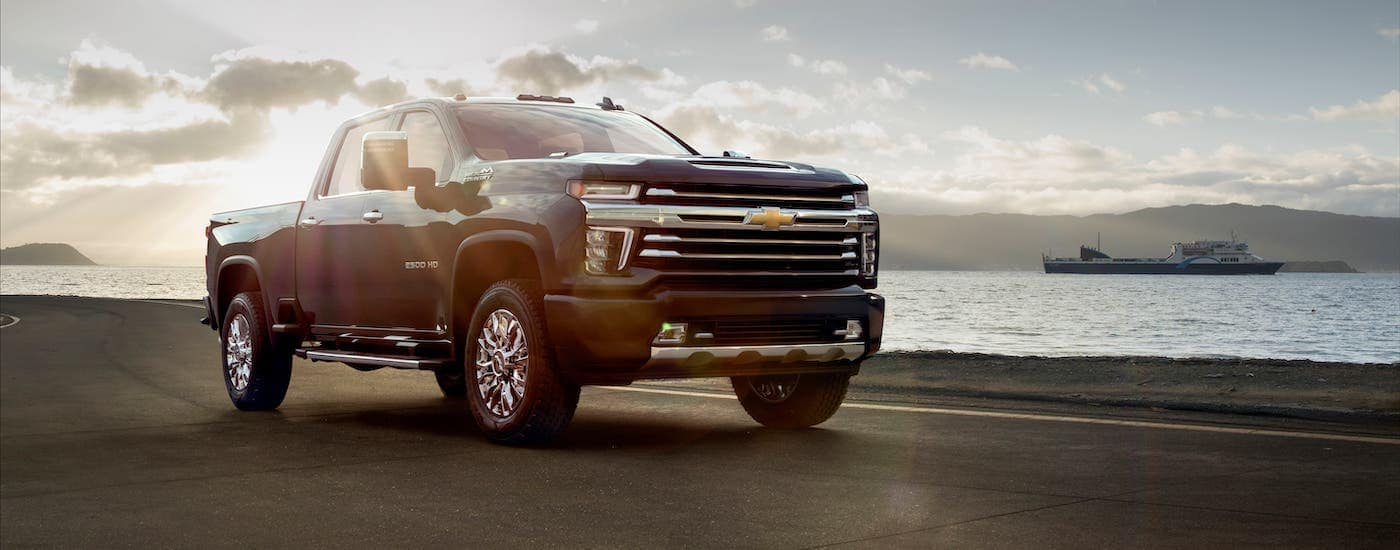 A backlit black 2020 Chevy Silverado 2500HD is parked in front of a river and large ship.