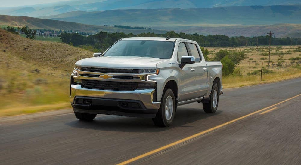 A silver 2020 Chevy Silverado LT is driving on a highway. Check out these great chevy trucks at a dealer in Indianapolis, IN.