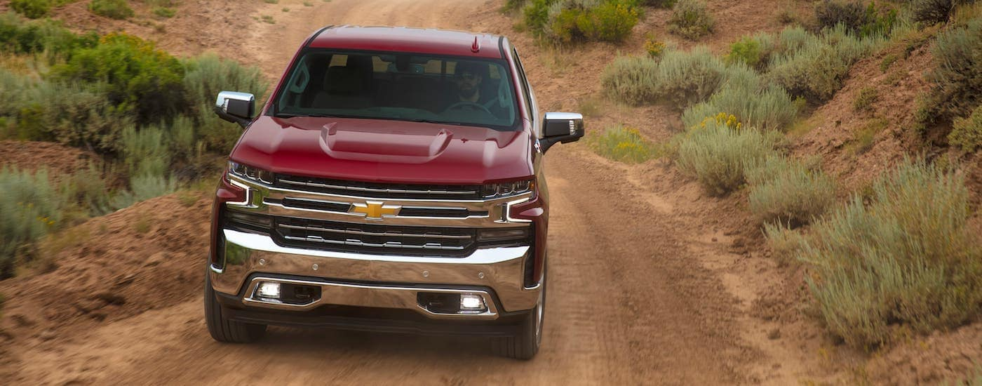 A red 2020 Chevy Silverado is shown driving through a field outside Indianapolis, IN, from the front.