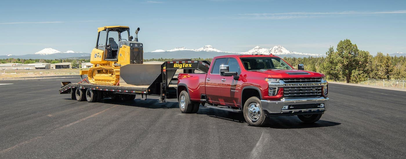 A red 2020 Chevy Silverado 3500 HD is parked on an airport runway and towing a trailer with a bulldozer.