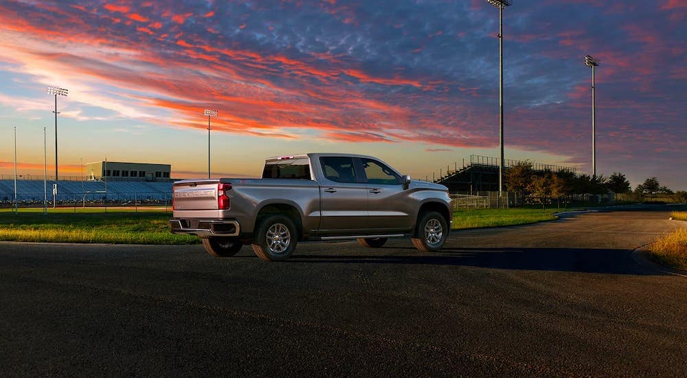A silver 2020 Chevy Silverado LT is parked in front of a football field at susnet.
