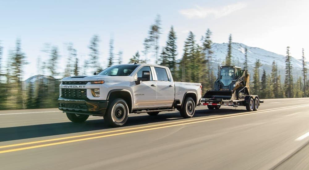 A white 2020 Chevy Silverado 2500HD is towing construction equipment on a forest highway.