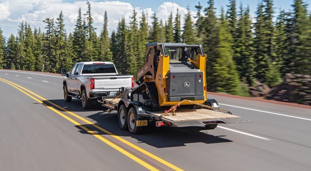 A white 2020 Chevy Silverado 2500HD is towing construction equipment on a forest highway, shown from the rear.