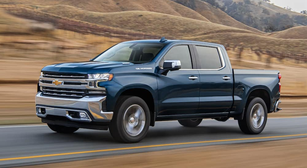 A blue 2020 Chevy SIlverado 1500 is driving past rolling hills after leaving a Greenwood Chevrolet dealer.