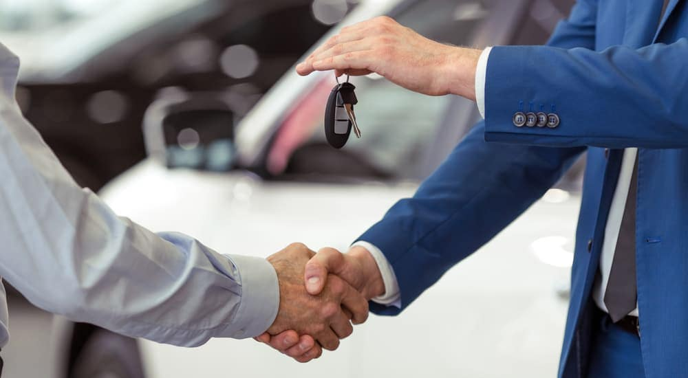 A salesman is shaking hands with a customer and handing car keys over after the buyer learned about how to buy a car with bad credit in Indianapolis, IN.