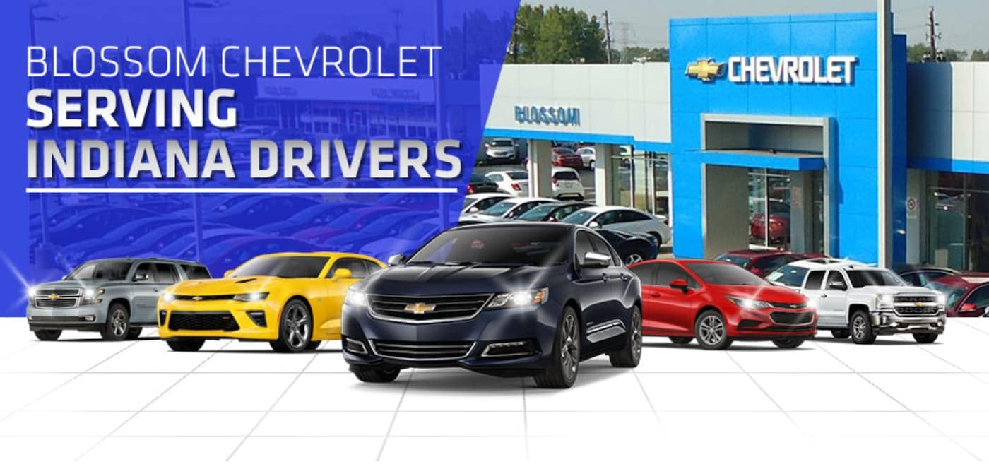 Five Chevy models are in front of the Indiana Chevy dealership, Blossom Chevrolet, with the words 'Blossom Chevrolet Serving Indiana Drivers' written above.