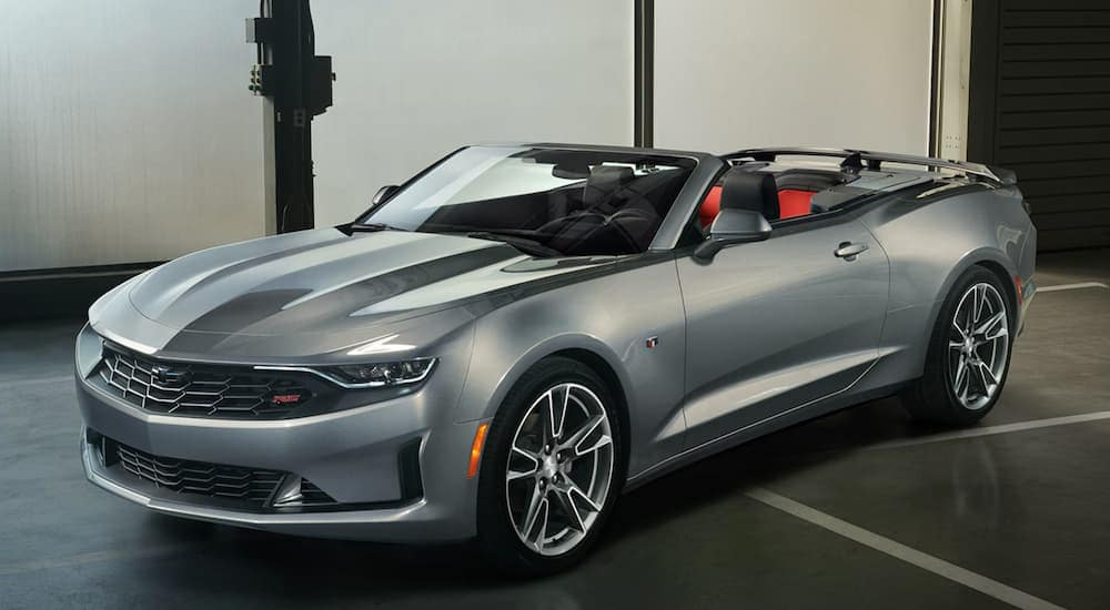 A silver 2020 Chevy Camaro is parked in a dark showroom at a Lawrence Chevrolet dealership.