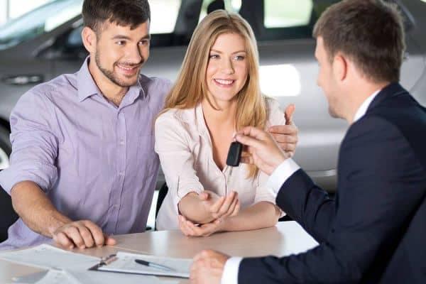 Car Salesperson handing a couple some car keys