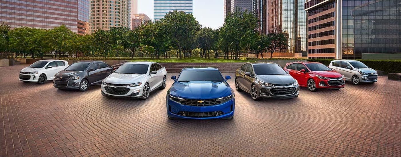 The Chevy lineup of sedans is parked in front of a city park.