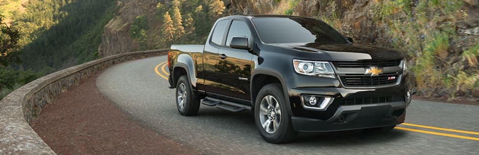 A black 2019 Chevy Colorado is being driven around a corner past trees on a test drive.