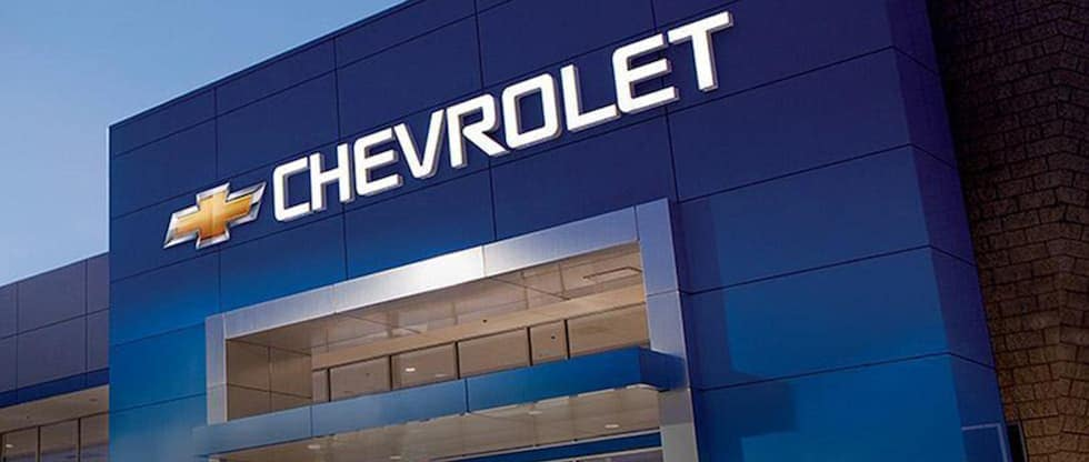 A Chevrolet sign is on a building where you can schedule your test drive.