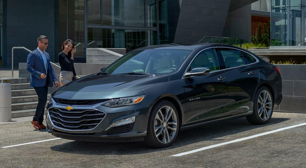 A couple is walking toward. grey 2019 Chevy Malibu in an Indianapolis, IN parking lot.