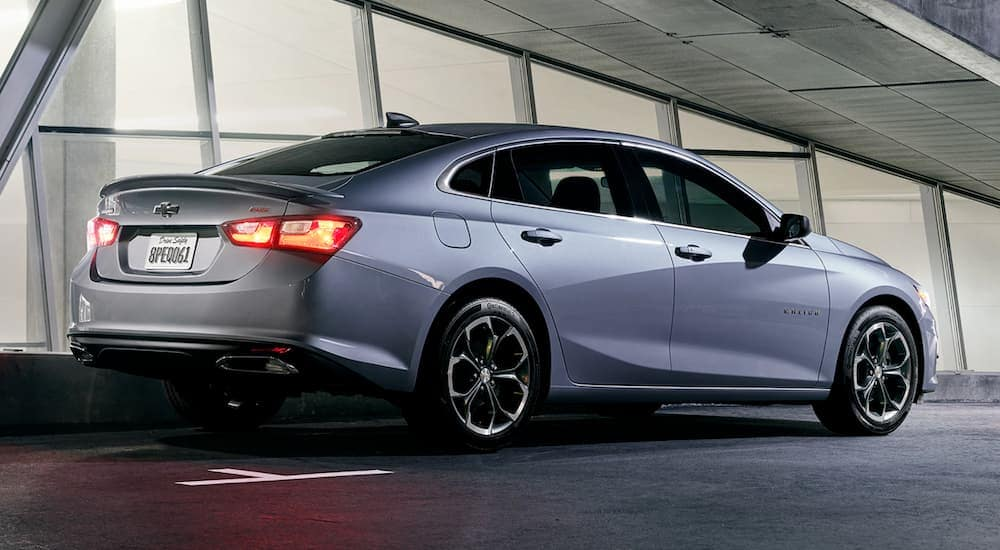 A silver 2019 Chevy Malibu is parked outside a lit up building at night.