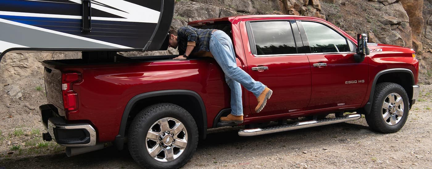 A man is reaching into the bed of a red 2020 Chevy Silverado 2500 hooked up to a 5th-wheel camper near Indianapolis, IN.