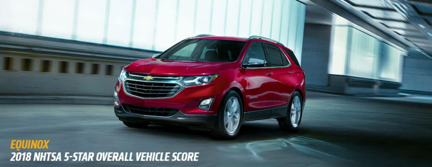 A red 2018 Chevy Equinox is driving past a lit building at night with the award listed below.