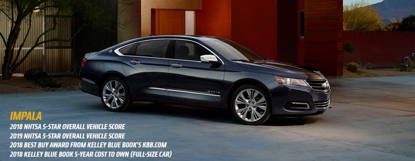 A dark grey 2018 Chevy Impala is parked at a modern home with the awards listed below.