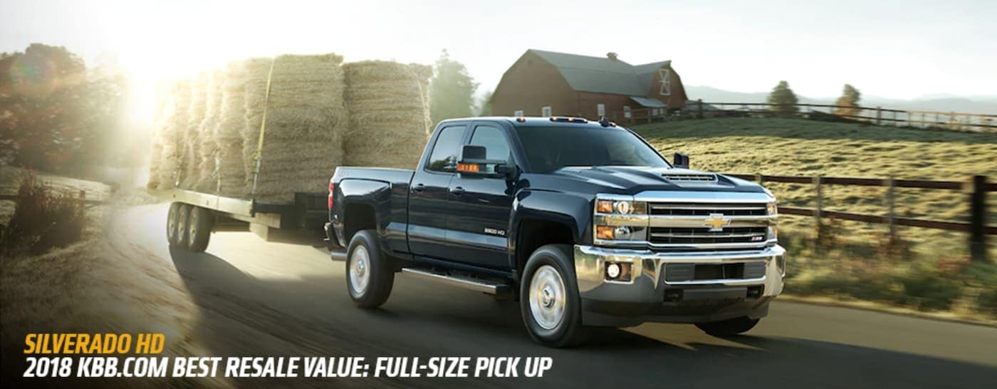 A black 2018 Chevy Silverado HD is towing hay bales past a farm with the award listed below.