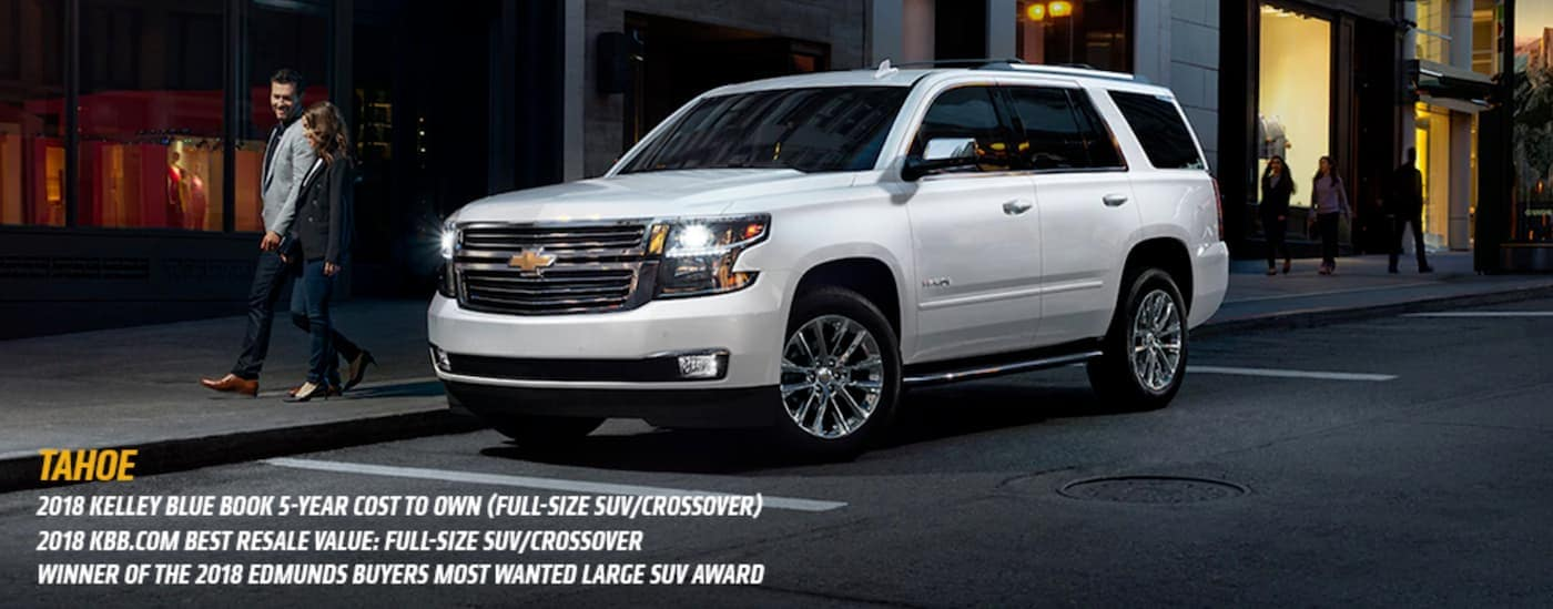 A white 2018 Chevy Tahoe is parked on a city street near Indianapolis, IN, at night with the awards listed.