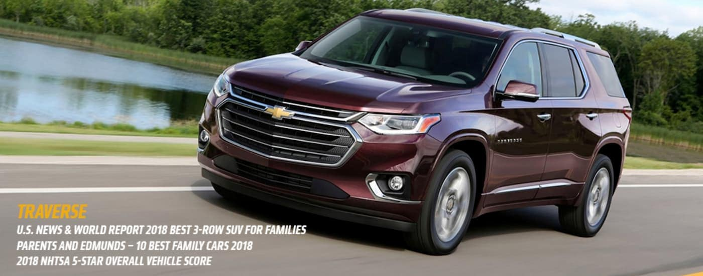A burgundy 2018 Chevy Traverse is driving past a pond with the awards listed below.