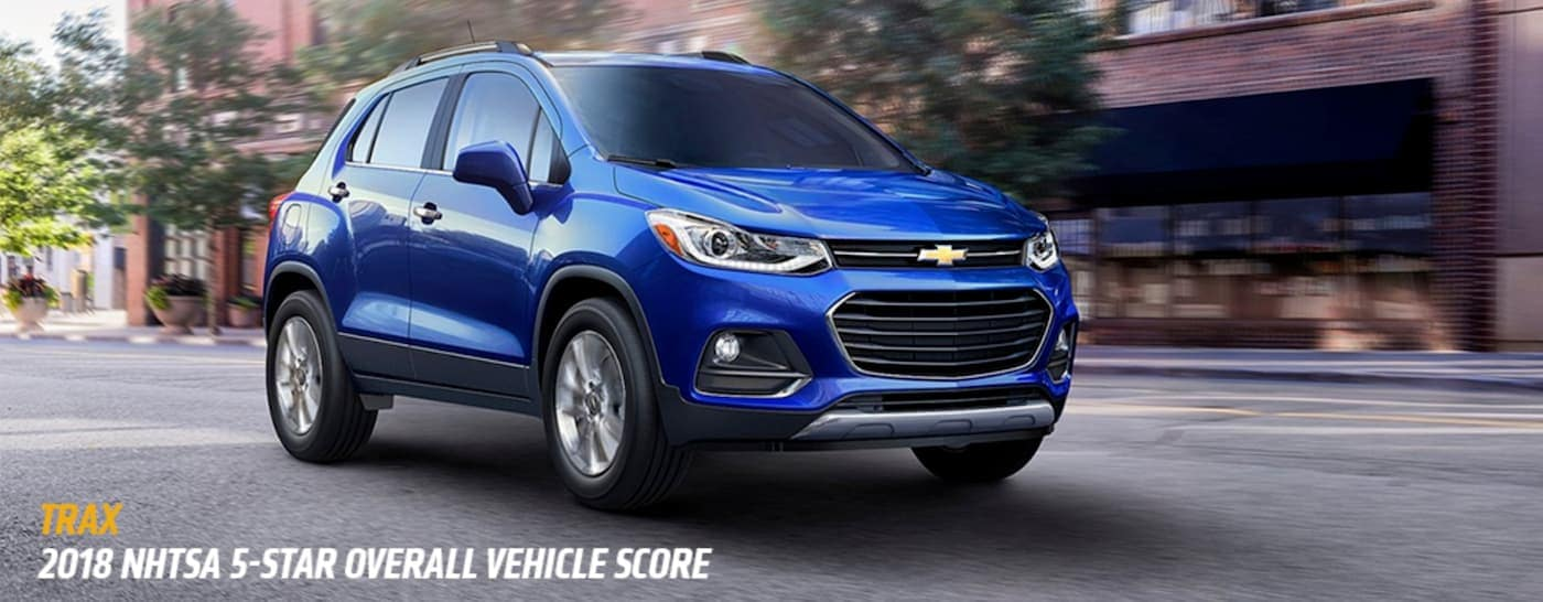 A blue 2018 Chevy Trax is driving on a city street with the award listed below.