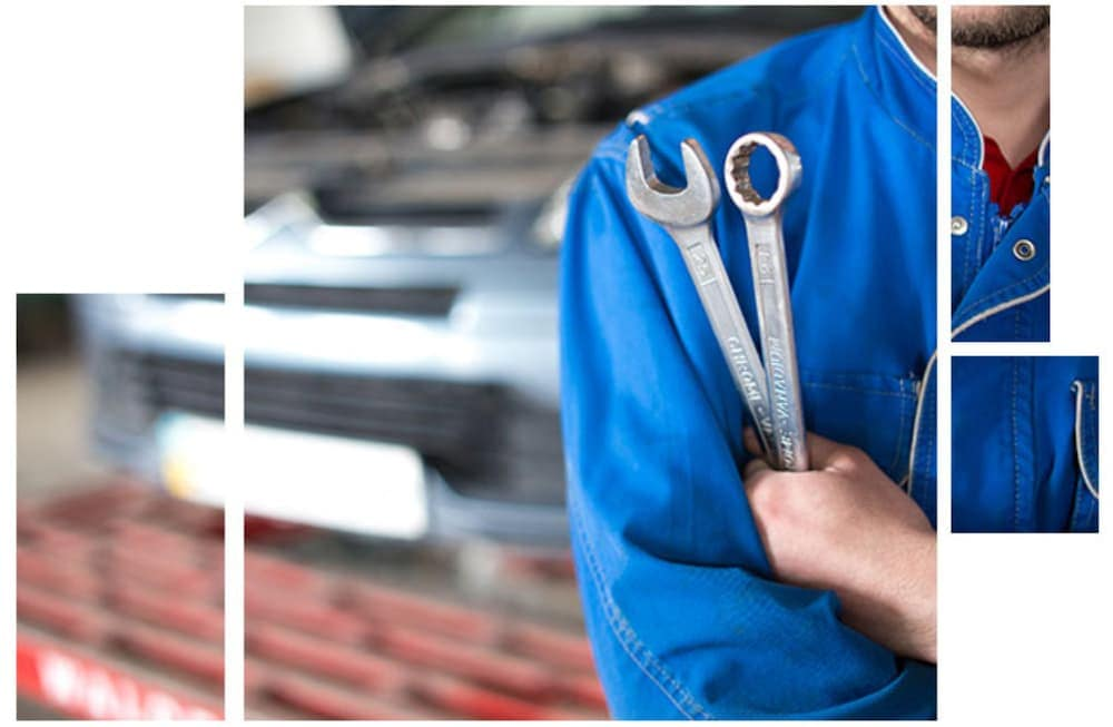 A mechanic is holding wrenches against his blue shirt.