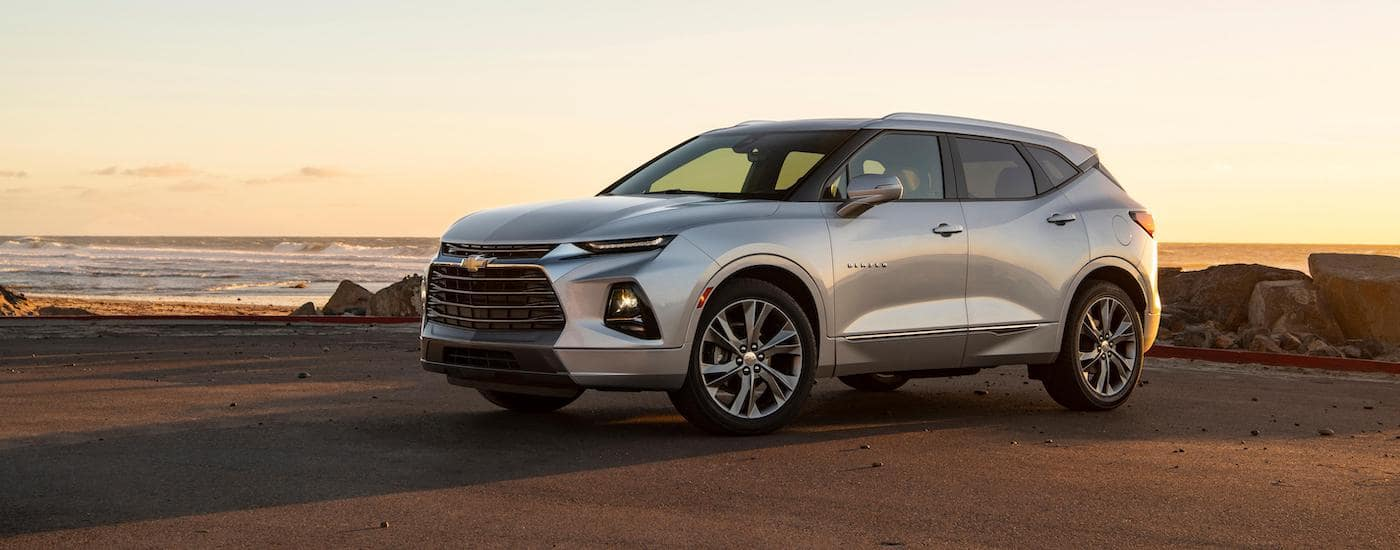 A silver 2020 Chevy Blazer is parked in front of a beach at sunset.