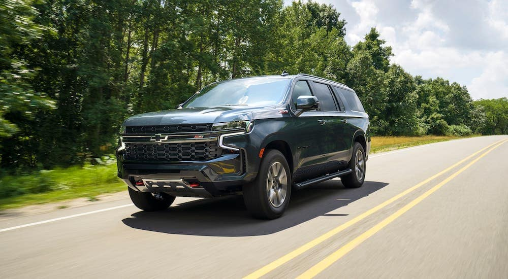 A new Chevy SUV, a gray 2021 Chevy Suburban Z71, is driving on a highway near Indianapolis, IN.